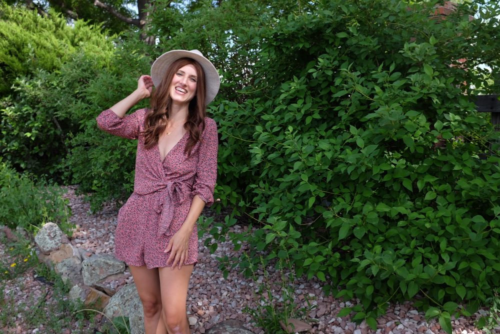 woman holding beige fancy felt hat in pink romper