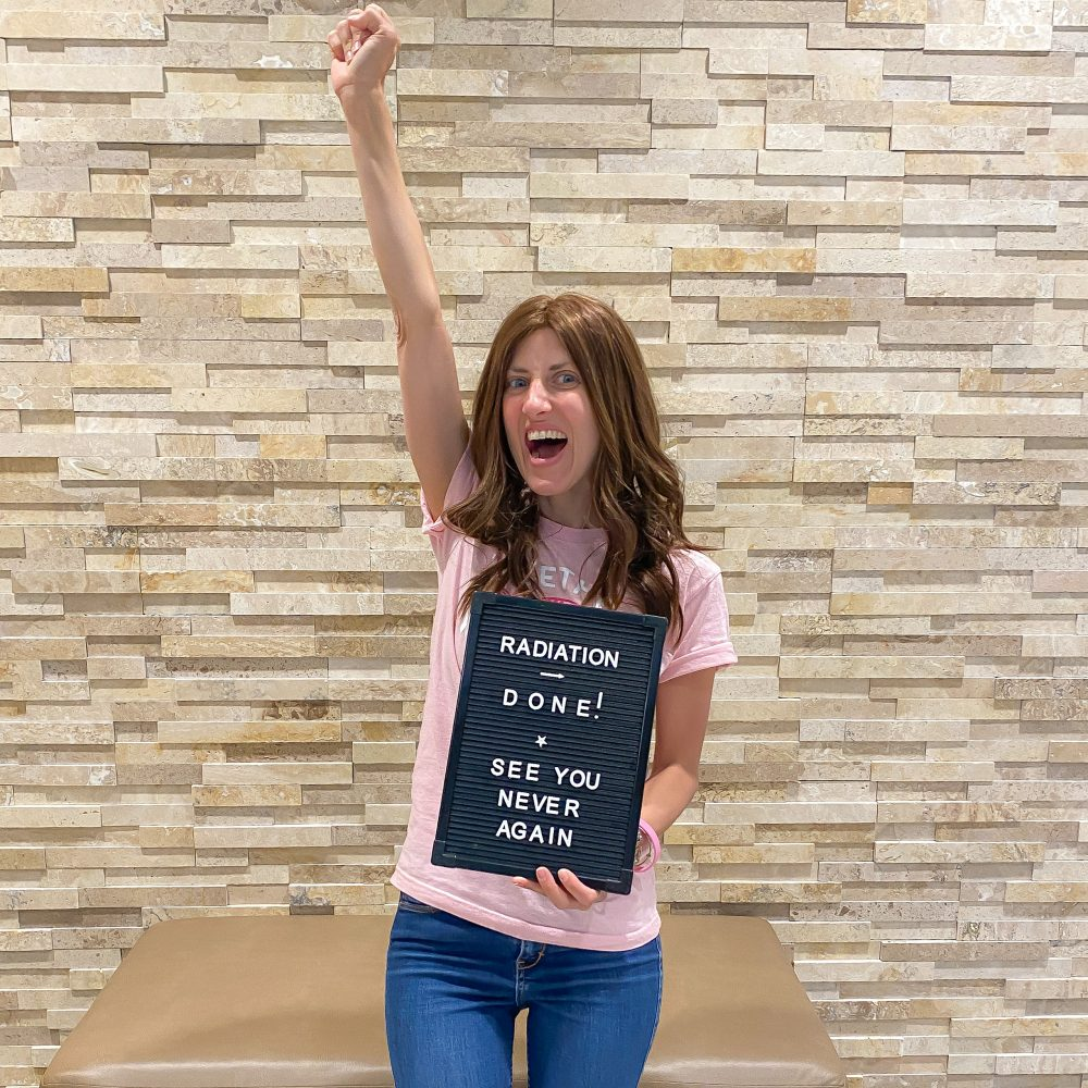 women in pink shirt holding a letter board saying done with radiation