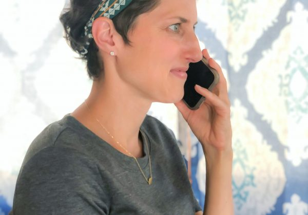 lady in grey dress and headband talking on a cell phone