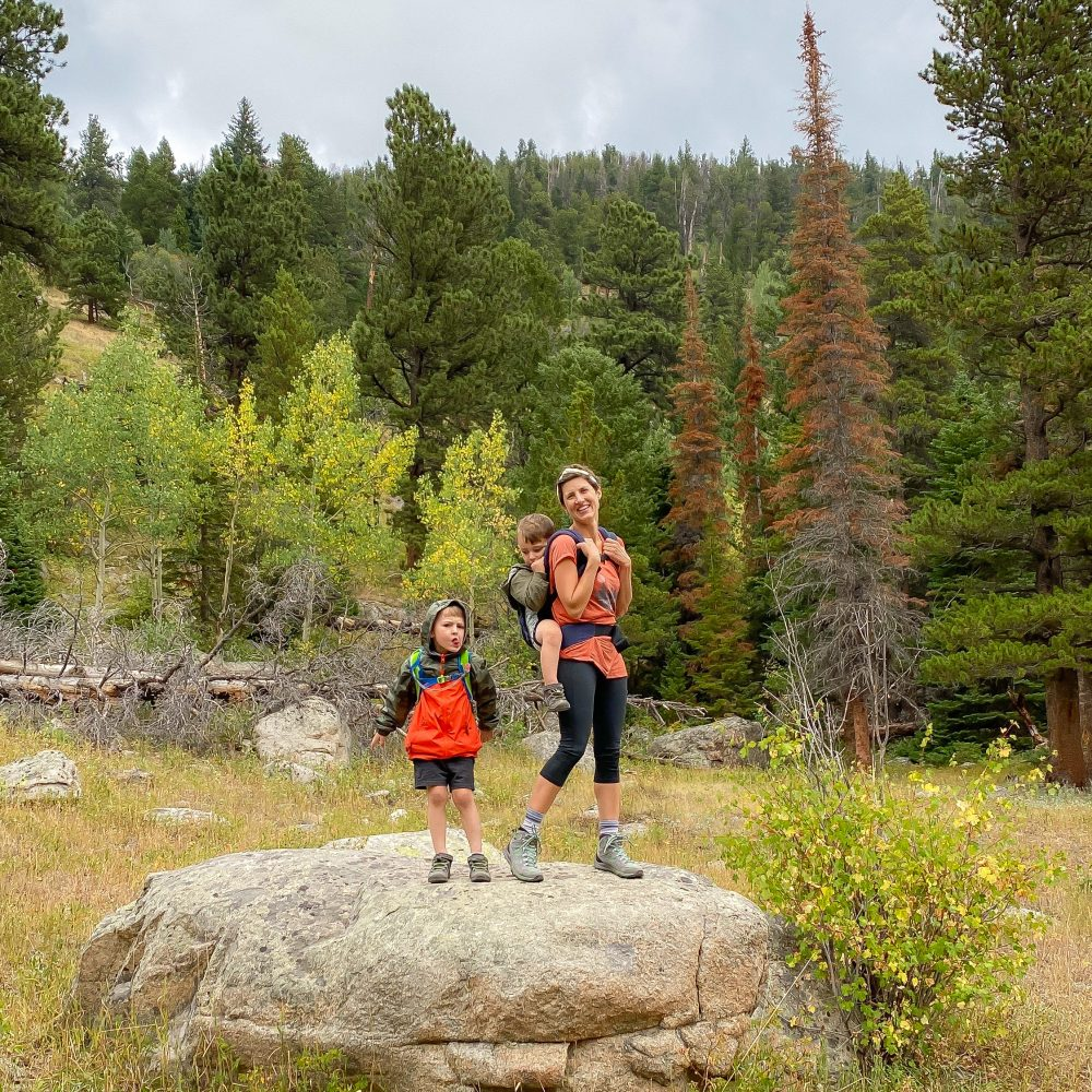 mom with a young kid on her back and a boy standing next to her in the middle of green lush scenery for a top places to camp in colorado blog post