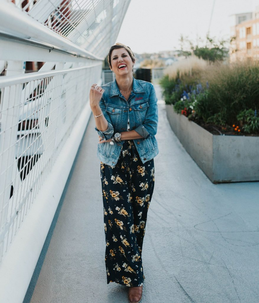 woman wearing a floral dress with a jean jacket laughing at the camera for a blog post titled closet staples to transition to fall