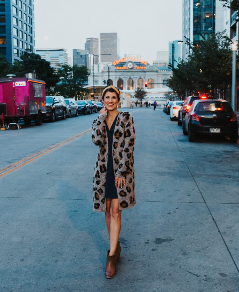 woman wearing an animal print cardigan over a blue dress and with booties for blog post titled cloest staples to transition into fall by Sabrina Skiles