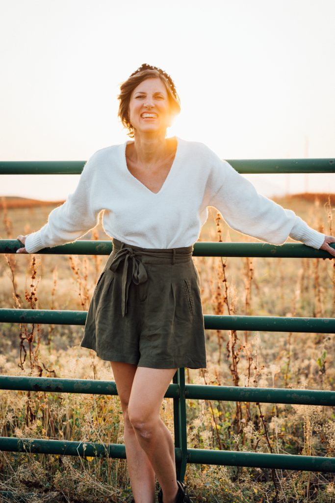 woman wearing a white sweater with shorts or a dress for blog post titled closet staples to transition into fall by Sabrina Skiles