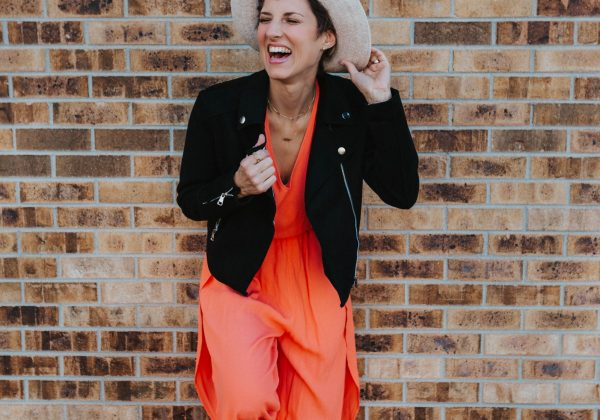 woman wearing hat laughing to the left wearing orange jumpsuit with black jacket for closet staples to transition to fall blog post