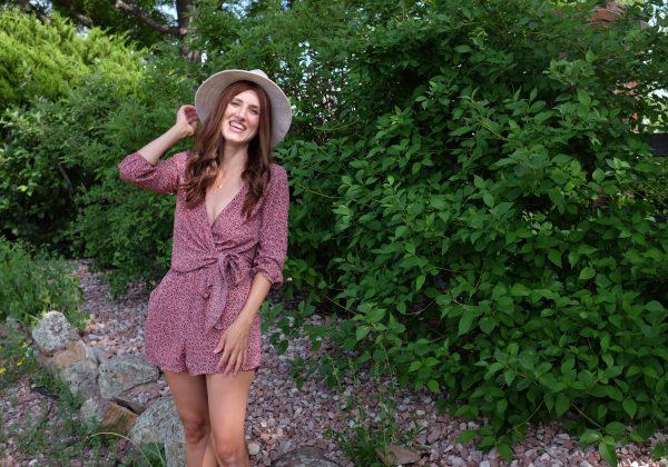 woman holding beige fancy felt hat in pink romper